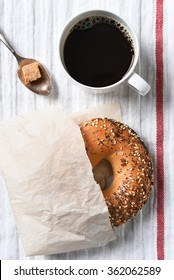 Fresh bagel, hot cup of coffee and spoon with lump of brown sugar on a tea towel. High angle view in vertical format.