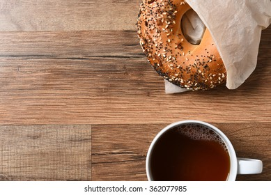 Fresh bagel and hot cup of coffee on a rustic wood table with copy space.