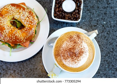 Fresh bagel with salad and smodel fish salmon and cup of coffee. Breakfast in a cafe or restaurant. Healthy food.