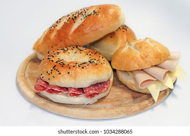 Fresh  Bagel and sandwich for breakfast. Bagel salami, Ham & Cheese burger and hot dog served on plate on a wooden tray