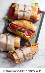 Fresh baguette sandwich bahn-mi styled. Bacon, roasted cheese, tomatoes and lettuce on metallic tray on white marble background.