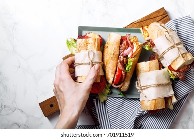 Fresh baguette sandwich bahn-mi styled. Bacon, roasted cheese, tomatoes and lettuce on metallic tray on white marble background. Female hand holding sandwich top view.