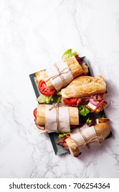 Fresh baguette sandwich bahn-mi styled. Bacon, roasted cheese, tomatoes and lettuce on metallic tray on white marble background. Vertical composition.