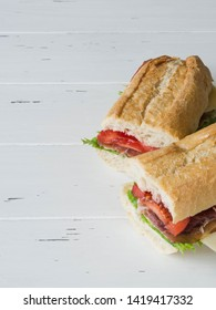 Fresh baguette sandwich with  meat, sliced cheese, tomatoes and fresh lettuce on white wood background.  copy space
