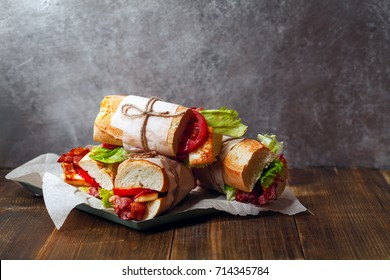 Fresh baguette sandwiches bahn-mi styled with bacon, roasted cheese, tomatoes and lettuce on wooden background