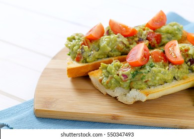 fresh baguettes with guacamole and tomatoes on wooden cutting board - close up