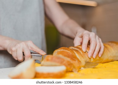 Fresh baked baguette bread on wooden cutting board - making sandwiches