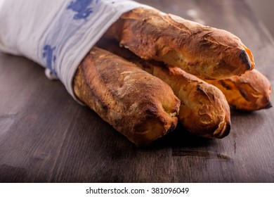 Fresh baked baugetts lined in a kitchen towel