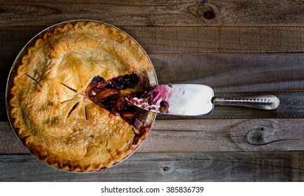Fresh baked blueberry and peach pie sitting on a wooden surface, overhead shot.