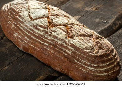 Fresh baked bread at brown wooden table. brown coarse grain bread