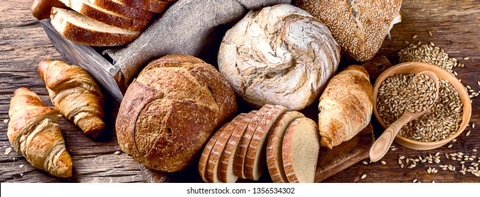 Fresh baked bread on rustic wooden background. Panorama, banner
