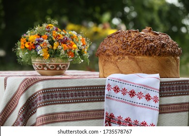 Fresh baked bread on a table with an embroidered tablecloth. Holiday Village Courtyard