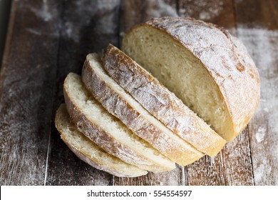 Fresh baked bread and sliced bread on rustic wooden table