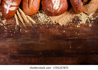 Fresh baked brown bread on a brown wooden background. Freshly baked traditional bread on a dark background.