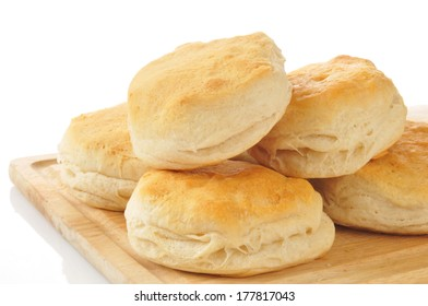 Fresh baked buttermilk biscuits on a cutting board with a white background
