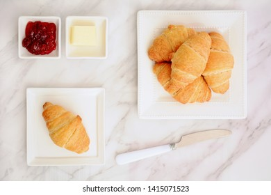 Fresh baked buttery flaky croissants with butter and cherry jam on marble background in flat lay composition.