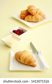 Fresh baked buttery flaky croissants with butter and cherry jam on marble background.