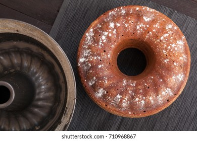 Fresh baked cake with chocolate in a round form on black background