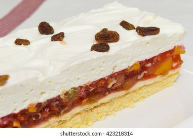 Fresh baked cake with mixed fruit jelly and whipped cream topping.