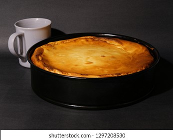 Fresh baked cheesecake in a brook shape, with a coffee cup.