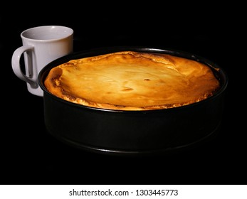 Fresh baked cheesecake in a brook shape, with a coffee cup, black background.