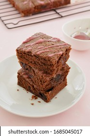 Fresh baked cherry chocolate brownies drizzled with cherry glaze stacked on plate on pale pink background.  Vertical format with focus on front of brownies
