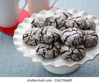 Fresh baked chocolate crinkle cookies for a Christmas treat. White ruffled cake stand. Horizontal format natural light