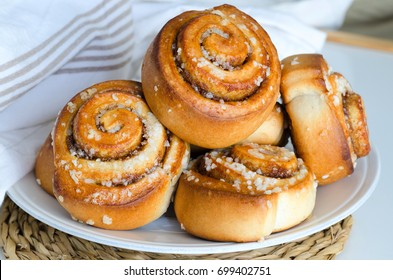 Fresh baked cinnamon rolls served on white plate. Homemade cinnamon buns for breakfast. Swedish sweet pastry background.