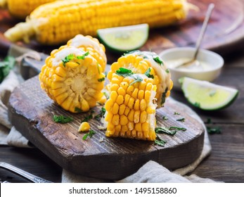 Fresh baked corn cobs with aioli sauce and cilantro on rustic wooden background. Healthy vegetarian food.