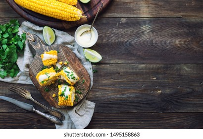 Fresh baked corn cobs with aioli sauce and cilantro on rustic wooden background. Healthy vegetarian food. Top view. Space for text.