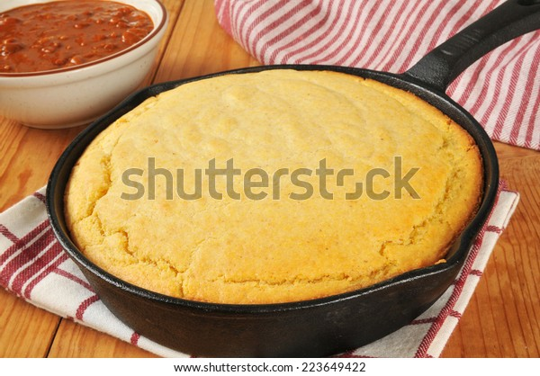 Fresh baked cornbread in a cast iron skillet with a bowl of chili