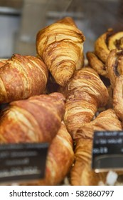 Fresh baked croissant pastry on sale in cafe.Empty price tag frames.Buy tasty bakery product for coffee break.Sweet dessert food.Vertical shot