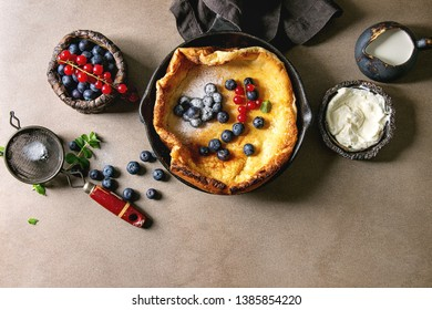Fresh baked Dutch baby pancake in iron cast pan served with blackberry and red currant berries, mascarpone cheese, sugar powder, jug of cream, vintage sieve over beige background. Flat lay, space