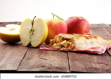 fresh baked homemade apple strudel with powdered sugar and mint leaves on table