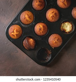 Fresh baked homemade lemon cakes muffins in black baking dish over dark texture background. Top view, space. Square image
