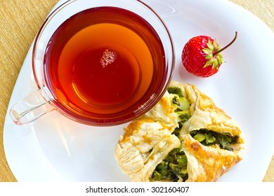 Fresh baked homemade puff pastry cakes, strawberry with fresh strong black tea in glass cup. Top view