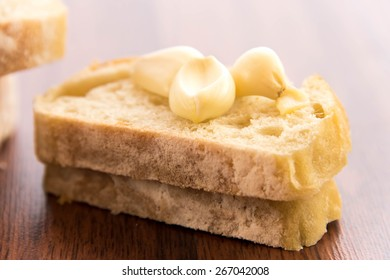 a fresh baked loaf of bread with whole cloves of roasted garlic