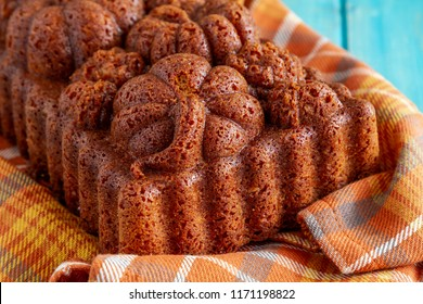 Fresh baked loaf of pumpkin bread baked in decorative fall themed pan sitting on orange plaid towel on blue wooden table