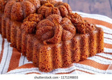 Fresh baked loaf of pumpkin bread baked in decorative fall themed pan sitting on orange striped towel