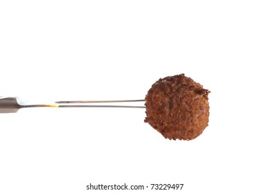Fresh baked meatball on a fork aginst a white background