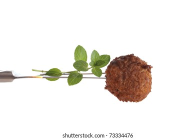 Fresh baked meatball on a fork against a white background