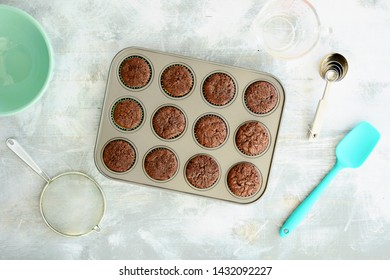 Fresh baked mini brownies in muffin tin with utensils in horizontal format and flat lay composition.