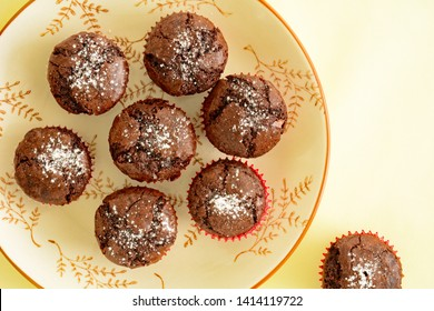 Fresh baked mini chocolate brownies sprinkled with icing sugar on pretty round plate in horizontal  composition.