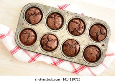 Fresh baked mini chocolate brownies in vintage muffin tin on red and white tea towel in flat lay composition.