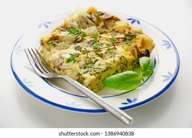 Fresh baked mushroom cheese quiche slice on blue and white plate in horizontal format,  Thyme and basil garnish.