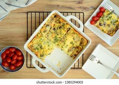 Fresh baked mushroom quiche with cherry tomatoes and side plates with forks.  Shot from overhead in flat lay composition.