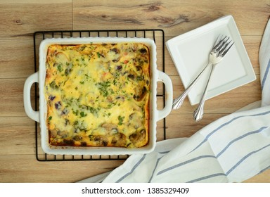Fresh baked mushroom quiche with side plates and forks.  Shot from overhead in flat lay composition.