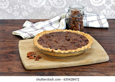 Fresh baked pecan pie, with a jar of pecans  in the background.