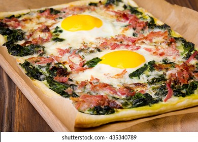 Fresh baked puff pastry egg, spinach, cheese, bacon tart served on wooden table. Traditional homemade european cuisine.
