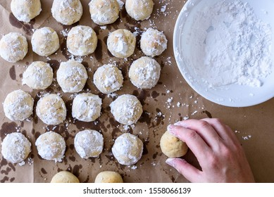 Fresh baked Russian Tea Cake cookies cooking on brown paper, woman's hand, bowl of powdered sugar ready to roll cookies in